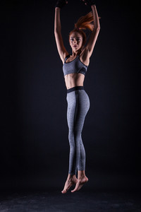 Fitness girl doing jumping pose while she's at a studio photoshoot. Beautiful spirit and body.