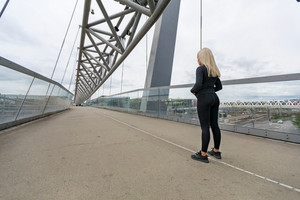 Fitness woman runner rests before running intervall workout on bridge