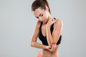 Fitness woman with pain in cubit over gray background