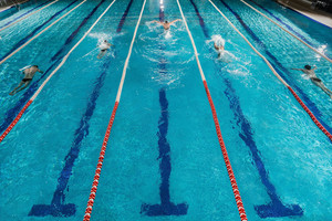 Five male swimmers doing the butterflies stroke while racing against each other in a swiming pool