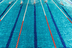 Five male swimmers racing against each other in a swiming pool