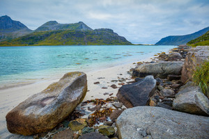 Fjord in rainy weather. Rocky beach in evening, White sand on the beach. Beautiful nature of Norway. Lofoten islands