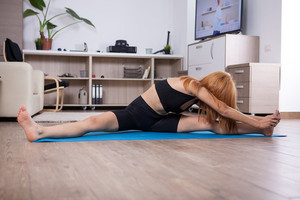 Flexible young woman doing split during her stretching program. indoor home training.
