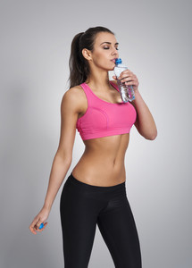Focus woman drinking water after workout