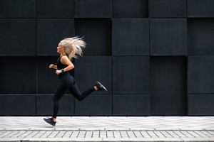 Focused woman running on the city street in modern environment