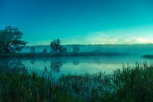 Foggy morning. Lake before sunrise. Rural landscape, mystical feeling