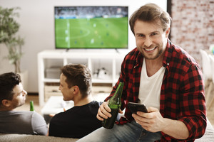Football fans with mobile phone and beer