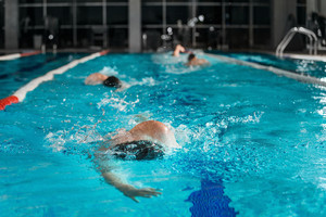 Four male swimmers swimming in the same lane in a pool