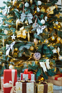 Fragment of decorated Christmas tree and pile of gift-boxes
