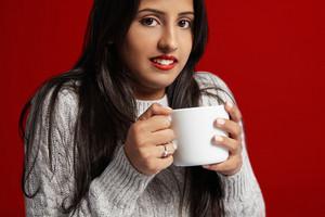 freezed woman drinks hot tee wears knitted sweater