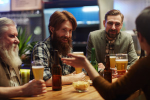 Friendly guys with beer spending evening in pub