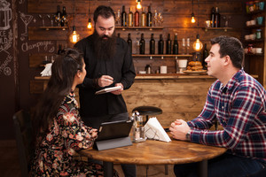 Friendly waiter is taking order from beautiful young couple. Vintage pub.