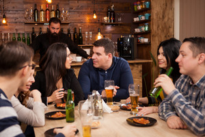 Friends in the pub drinking beer talking and having fun. Hipster pub.
