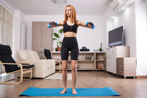 Front shoulder rises training during woman workout. Happy athlete girl.