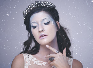 Front view of woman in frosty make up among snow falling