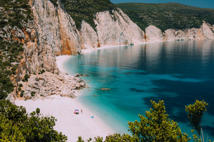 Fteri beach. Blue lagoon with rocky coastline, Kefalonia, Greece. Calm clear blue emerald green turquoise sea water with dark deep pattern