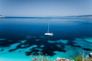 Fteri beach, Cephalonia Kefalonia, Greece. White catamaran yacht in clear blue transparent sea water surface