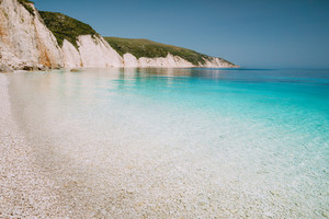 Fteri beach in Kefalonia Island, Greece. One of the most beautiful untouched pebble beach with pure azure emerald sea water surrounded by high white rocky cliffs of Kefalonia