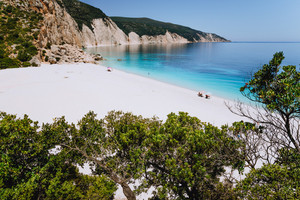 Fteri beach, Kefalonia, Greece. Lonely tourists under umbrella chill relax near clear blue emerald turquoise sea water lagoon. Framed by tree foliage