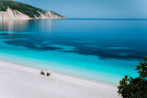 Fteri beach, Kefalonia, Greece. Lonely unrecognizable tourist couple hiding from sun umbrella chill relax near clear blue emerald turquoise sea water lagoon