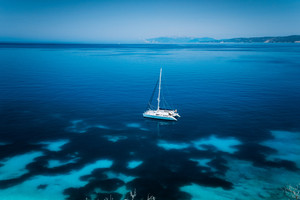 Fteri beach Kefalonia, Greece. White catamaran yacht in clear blue transparent sea with dark pattern water surface
