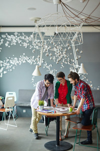 Full body shot of team of young creative people wearing casual clothes collaborating at meeting in modern office standing round small table and looking at supplies laid out on it