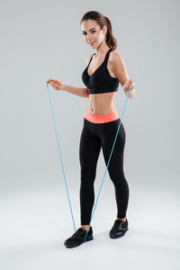 Full length image of a smiling fitness woman doing exercise with skipping rope over gray background