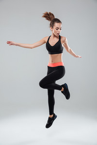 Full length image of a sports woman jumping in studio over gray background