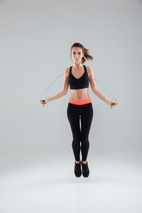 Full length image of a young fitness woman jumping with skipping rope over gray background