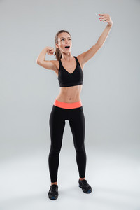 Full length image of funny fitness woman making selfie on her smartphone while winks and showing her bicep at camera over gray background
