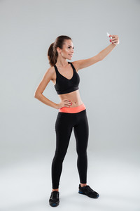 Full length image of smiling fitness woman making selfie while holding arm on hip over gray background