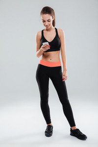 Full length image of smiling fitness woman using smartphone over gray background