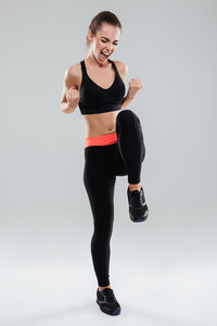 Full length image of So happy screaming fitness woman over gray background