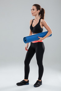 Full length image of surprised fitness woman with fitness mat oer gray background