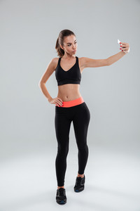 Full length picture of fitness woman posing and making selfie on her smartphone over gray background