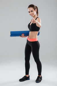 Full length picture of happy fitness woman holding fitness mat and pointing at the camera over gray background