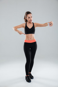 Full length picture of happy fitness woman pointing at abdominals and making selfie over gray background
