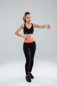 Full length picture of happy fitness woman showing thumb up while making selfie on her smartphone over gray background
