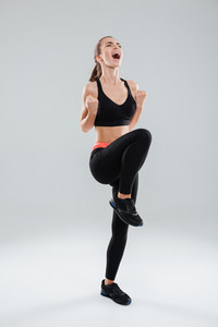 Full length picture of happy screaming fitness woman over gray background