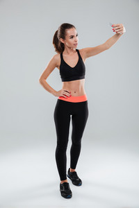 Full length picture of smiling fitness woman posing and making selfie on her smartphone while holding arm on hip over gray background