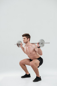 Full length portrait of a healthy fit man athlete doing squat exercises with barbell isolated over white background