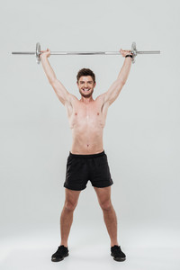 Full length portrait of a young fit sportsman lifting heavy barbell isolated over white background