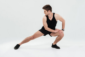 Full length portrait of a young healthy man warming up before gym isolated on a white background