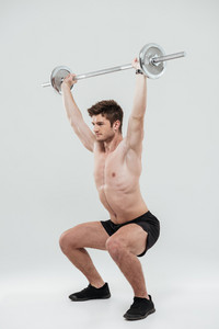 Full length portrait of a young strong sportsman doing squat exercises with barbell isolated over white background