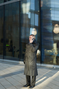 Full-length portrait of mature entrepreneur having phone conversation while standing at modern glass office building