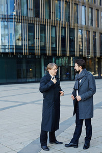 Full-length portrait of two middle-aged businessmen in coats standing at modern office building and discussing their future joint project
