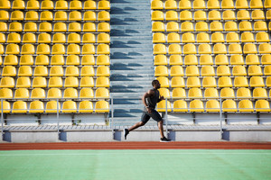 Full length side view of a sportsman running on a racetrack at the stadium