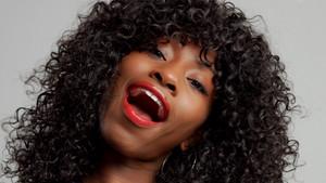 fun black woman with big curly afro hair making fun faces
