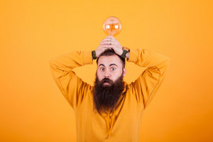 Funny bearded man with a light bulb over his head in front over yellow background. Great mind. Smart man. Great solution