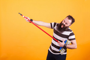 Funny bearded rockstar playing virtual guitar with broom over yellow backgrounnd. Handsome man. Cheerul man.